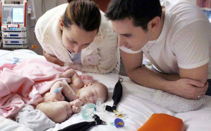 Супруги Карлсон смотрят на своих новорожденных дочерей